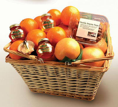Two-handled wicker basket filled with oranges, tangaerines, grapefruit, chocolate amaretto pecans, tropical marmalades and jelly, orange blossom perfume and hersheys kisses